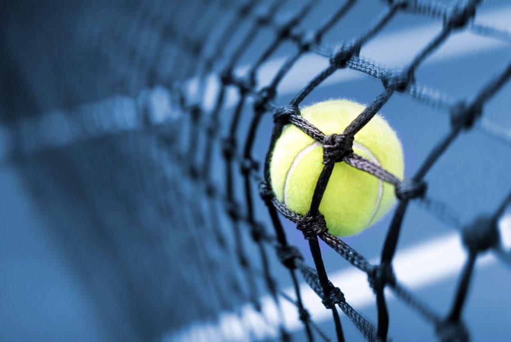 Pileczka tenisowa na tle siatki i kortu