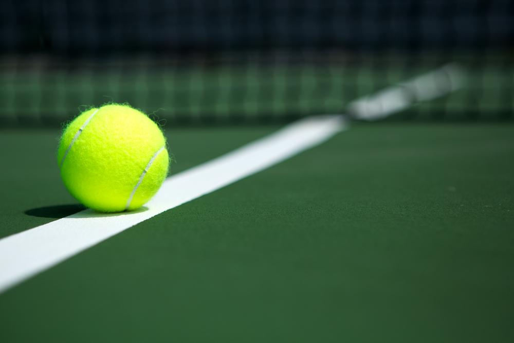 Piłka tenisowa na korcie z siatką w tle