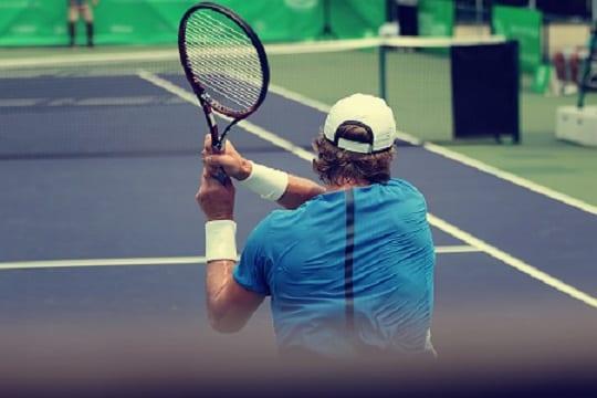 Tenisista tyłem odbijający piłeczkę