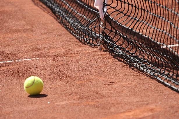 Pileczka od tenisa i kort ziemny z siatka