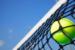 Piłeczka tenisowa w siatce na tle nieba